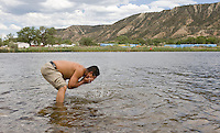leaving0627 Ruben Rosario, 33, of Chiapas, splashes water on his face while standing in a Colorado River reservoir located next to a Colorado rest stop. (Pat Shannahan/ The Arizona Republic)
