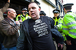 "© Joel Goodman - 07973 332324 . 02/04/2011 . Blackburn , UK . A man wearing a t-shirt reading "" Right wing extremists with shaven heads and quilted jackets "" is ejected from the demonstration . The English Defence League ( EDL ) hold a demonstration in Blackburn . Photo credit : Joel Goodman"