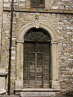 700 year old wooden door with inscription Pax Borvo 1226-1926 over the archway on the piazza del Comune, Assisi, Ital