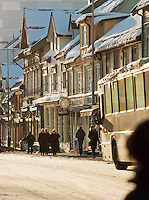 Shoppers stroll down the main street in the winter afternoon sun, in Tromso, Norway