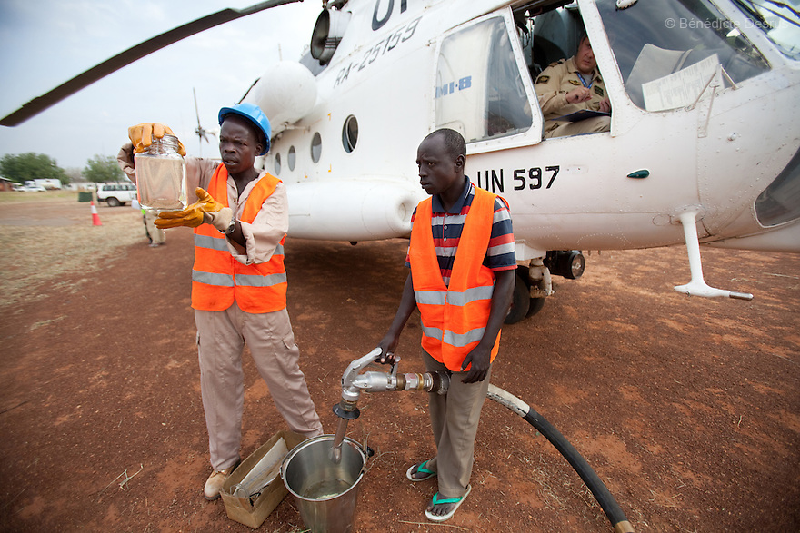 11 december 2010 - Riwoto, South Sudan - Sudanese men test oil before refueling a UN Mil Mi-8 helicopter. the UNMIS retrieves completed registration materials in Riwoto - Kapoeta North County, the day after registration for South Sudan's referendum closed. The referendum is scheduled to take place on January 9, 2010. Photo credit: Benedicte Desrus