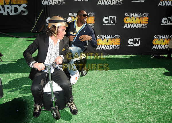 TERRELL OWENS .1st Annual Cartoon Network Hall of Game Awards held at Barker Hangar, Santa Monica, California, USA..February 21st, 2011.full length black blue cardigan sitting mouth open funny scooter ride wheels  sunglasses shades denim jeans.CAP/ADM/BP.©Byron Purvis/AdMedia/Capital Pictures.