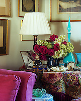 In this corner of the living room a circular side table is covered in a floral tapestry brought to life by an arrangement of roses and hydrangeas