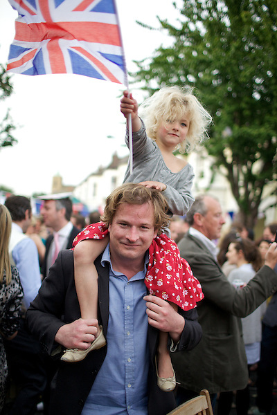 A young child waves a union jack flag while sitting on her father's shoulders during a Royal Wedding street party in London, England