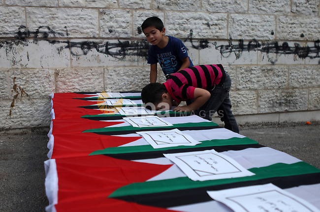 A Palestinian boy kisses a symbolic coffin during a protest in solidarity with Palestinians killed by Israeli forces in Gaza Strip, in the West Bank City of Ramallah July 22, 2014. A series of Israeli air strikes killed seven people in Gaza, including five members of the same family, an emergency services spokesman said. The deaths hike the total Palestinian toll to 583 since the Israeli military launched Operation Protective Edge on July 8 in a bid to stamp out rocket fire from Gaza. Photo by Shadi Hatem