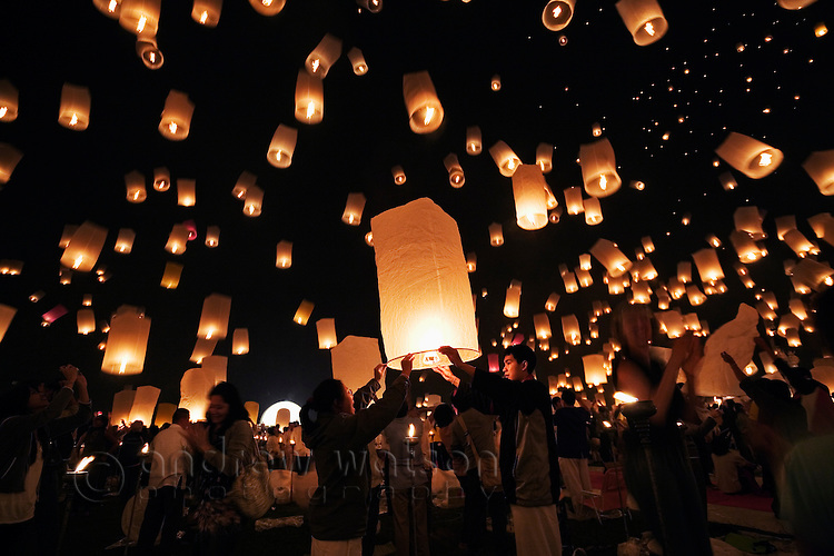 Revellers launch khom loi (sky lanterns) into the night sky during Yi Peng festivities - part Loi Krathong.  The khom loi are released in the belief that grief and misfortune will float await them. San Sai, Chiang Mai, THAILAND