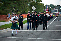 A bagpiper leads a parade of first responders and their vehicles across the Main Street Bridge wreath to First Responders Park in Westerville, OH, for ceremonies marking the 10th anniversary of the attack on the World Trade Center.