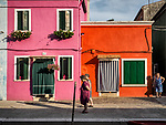 Old women walk past red and pink houses along the canal. The colorful village of Burano, Italy.