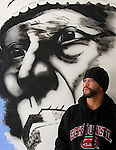 "Menominee Indian artist Kory ""Sack"" Sackatook, 33, stands beside an in-progress airbrush wall mural image at the Amerindian Center in Green Bay on December 4, 2006."