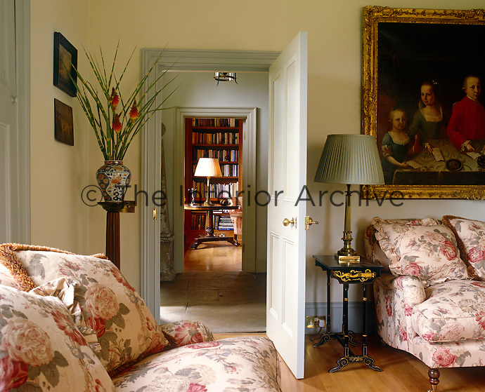 A comfortable sitting room on one side of the stone-flagged entrance hall with a view into the library