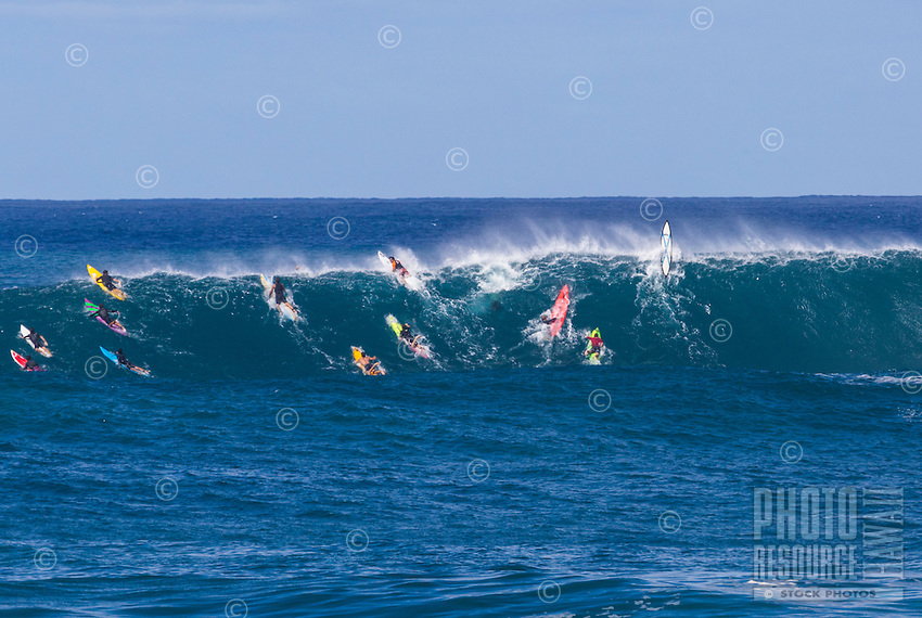 Surfers try to paddle over a huge wave at Waimea Bay, North Shore, O'ahu.
