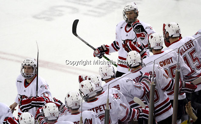 University of Nebraska Omaha's Terry Broadhurst and Matt Ambroz skate by the bench to celebrate a first period goal. (Photo by Michelle Bishop)