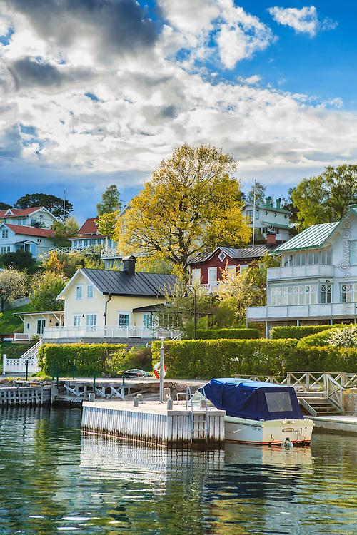 Båt vid brygga med villor vår på Dalarö i Stockholms skärgård.