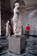 Paris, August 1977. Venus de Milo sculpture at Louvre Museum. August in Paris is a noveable feast. While millions of residents are leaving for their favourite resorts, thousands of foreign tourists are flocking to the French Capital. Nevertheless, genuine Parisians, old and young alike, stay in Paris and mantain the tradition charm.