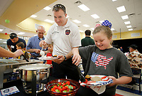 NWA Arkansas Democrat-Gazette/DAVID GOTTSCHALK  Jeremy Oxford, assistant fire chief with the Wheeler Fire Department, watches his daughter Addyson, a third grade student at Jerry Pop Williams Elementary School, select strawberries Tuesday, September 11, 2018, during the Honorary Breakfast for Local Heroes at the school in Farmington. The school invited emergency personnel, first responders, active and retired military personnel to a breakfast with third graders. The guests introduced themselves and gave a piece of advice followed by the students distributing hand made thank you cards.