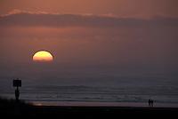A couple wanders along the beach during sunset near Long Beach, Washington Saturday Feb. 7, 2009.