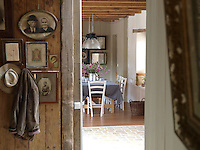 Seen from the entrance hall a table is laid for breakfast in the cosy dining room