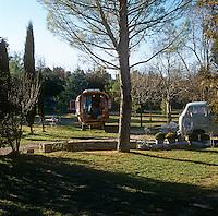 A gypsy caravan sits in a wooded garden.