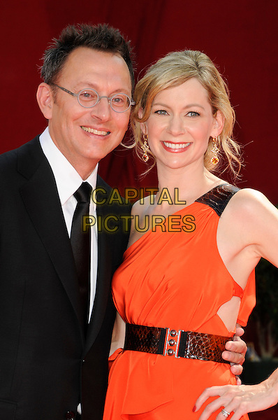 MICHAEL EMERSON & CARRIE PRESTON.Arrivals at the 61st Primetime Emmy Awards held at Te Nokia Theater in Los Angeles, California, USA. .September 20st, 2009 .emmys half length red orange one shoulder dress hand on hip black belt suit glasses couple.CAP/ROT.©Lee Roth/Capital Pictures