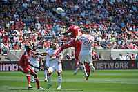 Chicago defender Jalil Anibaba heads a corner kick safely away from the goal in front of New York midfielder Joel Lindpere.  The Chicago Fire tied the New York Red Bulls 1-1 at Toyota Park in Bridgeview, IL on June 26, 2011.
