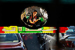 A Bangladeshi driver trying to catch some sleep is reflected on the mirror of his three-wheeler taxi halted due to a traffic jam in Dhaka, Bangladesh.