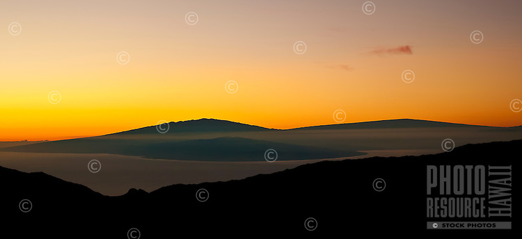 A very rare dawn view of the outline of Mauna Kea and the coast of the Big Island beyond the 'Alenuihaha Channel from the summit of Haleakala in Haleakala National Park, Maui.