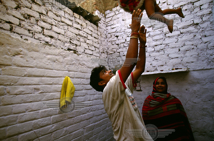 A father plays with his young son near their house in Shadipur Depot.