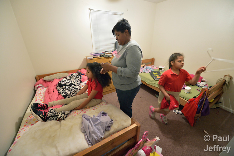 Sonnet Pichardo helps her daughters Rhinaye (left) and Savannah get ready for school in their bedroom early in the morning in their home in Columbus, Georgia. Pichardo successfully participated in Circles of Hope, a program to end poverty and build financial independence sponsored by the Open Door Community House in Columbus.