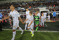 Kyle Naughton and other Swansea players walk onto the pitch before the Barclays Premier League match between Swansea City and Leicester City at the Liberty Stadium, Swansea on December 05 2015