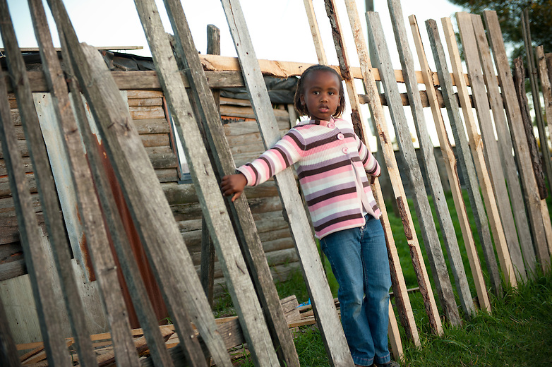 A young girl keeps vigil outside her shack. Shacks in this part of South Africa are mostly made out of wood from the local timber industry.