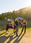 Old Bethpage, New York, U.S. 29th September 2013. A little girl enjoys the Pony Ride, one of the last rides open as closing time arrived at The Long Island Fair. A yearly event since 1842, the county fair is now held at a reconstructed fairground at Old Bethpage Village Restoration.