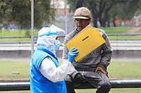BOGOTA, COLOMBIA - April 14:  A government worker wearing a protective suite against Coronavirus talks to a homeless Venezuelan man in Bogota, Colombia, Tuesday, April 14, 2020. Thousands of Venezuelan migrants were left on the streets of the main Colombian cities due to mandatory preventive quarantine decreed by the government to prevent the spread of the Covid-19 pandemic. (Photo by Daniel Munoz/VIEWpress)