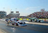 Sept. 21, 2012; Ennis, TX, USA: NHRA funny car driver Courtney Force (left) races alongside father John Force during qualifying for the Fall Nationals at the Texas Motorplex. Mandatory Credit: Mark J. Rebilas-US PRESSWIRE
