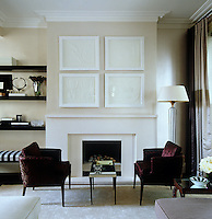 A pair of armchairs upholstered in a rich red fabric are placed in front of a contemporary marble fireplace