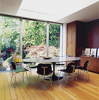 An extended dining area, with Eero Saarinen table and chairs by Charles and Ray Eames, overlooks a pretty garden with specimen trees. The flooring is an oak plank floor with a bevelled edge.
