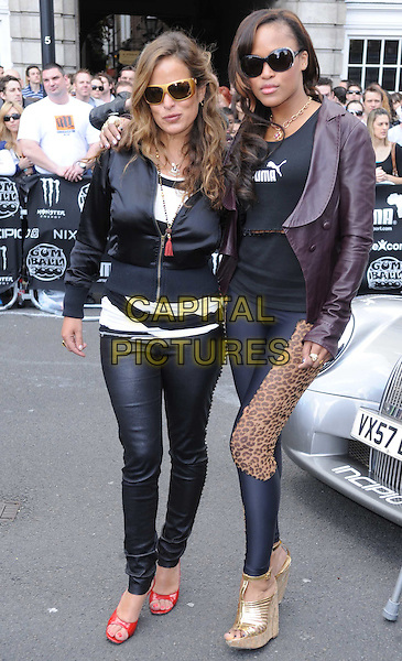 JADE JAGGER & EVE (Eve Jihan Jeffers) .The 2010 Gumball 3000 Rally, London, England..May 1st, 2010.full length black jacket trousers red wedges shoes sunglasses shades leather leggings leopard print brown gold wedges.CAP/DS.©Dudley Smith/Capital Pictures