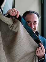 Chief designer Daniele Ceccomori hides behind one of the curtains in the living room made of menswear inspired herringbone edged with seatbelt material