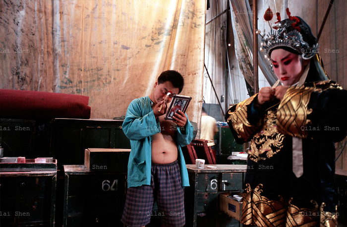 Opera079 20040721 SHANXI, CHINA: A Jin Opera actress buttons her costum of a young military officer backstage during a performance in a rural village in Shanxi Province, China 21 July 2004. Jin Opera actors often plays roles of the opposite sex on stage.