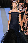 Emily walks runway in a indigo blue twisted tulle off the shoulder gown, by Monique Lhuillier, from the Monique Lhuillier Spring 2012 collection fashion show, during Mercedes-Benz Fashion Week Spring 2012.