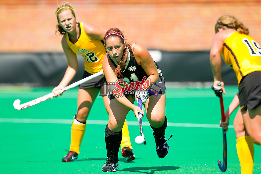 Jillian Anzalone (21) of the Wake Forest Demon Deacons passes the ball between two Iowa Hawkeye players during second half action at Kentner Stadium on August 25, 2012 in Winston-Salem, North Carolina.  The Hawkeyes defeated the Demon Deacons 3-2 in overtime.  (Brian Westerholt / Sports On Film)