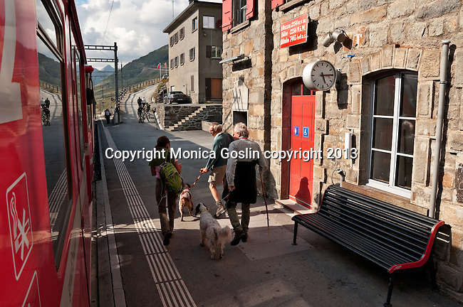 Swiss red Bernina Express trains stop at the the highest train station on the Bernina Express route, Ospizio Bernina, on the way to St. Moritz, Switzerland. The Ospizio Bernina train station is the highest train station on the train route at 2,253 meters