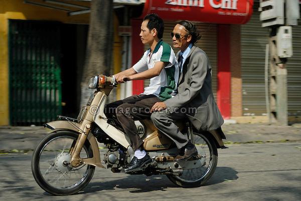 Asia, Vietnam, Hanoi. Hanoi old quarter. Two vietnamese men riding on small motorbike through Hanoi.