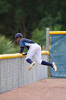 GCL Rays outfielder Christian Johnson (4) goes over the fence while catching a fly ball during a Gulf Coast League game against the GCL Pirates on August 7, 2019 at Charlotte Sports Park in Port Charlotte, Florida.  GCL Rays defeated the GCL Pirates 5-3 in the second game of a doubleheader.  (Mike Janes/Four Seam Images)