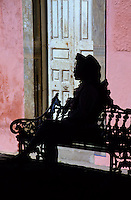 Silhouette of a mexican girl sitting on a cast iron bench in fron of a red house wall and door