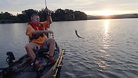 NWA Democrat-Gazette/FLIP PUTTHOFF <br /> Mike McBride catches a crappie at sunrise Sept. 24 2015 at Lake Sequoyah. He caught several using a jig under a bobber. Crappie fishing improves at the lake as the water cools, McBride said.