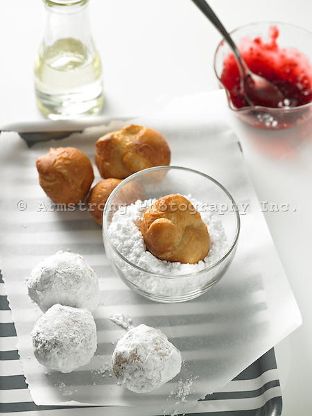 Doughnut holes being coated in powdered sugar, with jelly.
