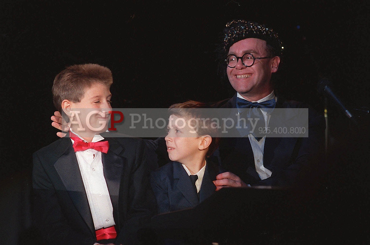 "Jul 09, 1988 - Los Angeles, California, United States - Singer Elton John is joined by Ryan White, left, and Jason Robertson, both suffering from AIDS July 9, 1988 as he performs at ""For The Love of Children,"" a benefit for children with AIDS, and other serious illnesses or problems, at the Century Plaza Hotel in Los Angeles, July 9, 1988.  John appeared on  stage for the first time in two years..(Credit Image: © Alan Greth)"
