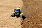 Farmer ploughing recently harvested  field of crops.