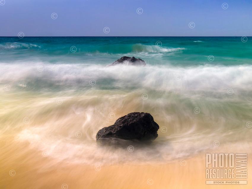 Waves rush around two shoreline rocks on a sunny day at Makalawena Beach, Big Island.