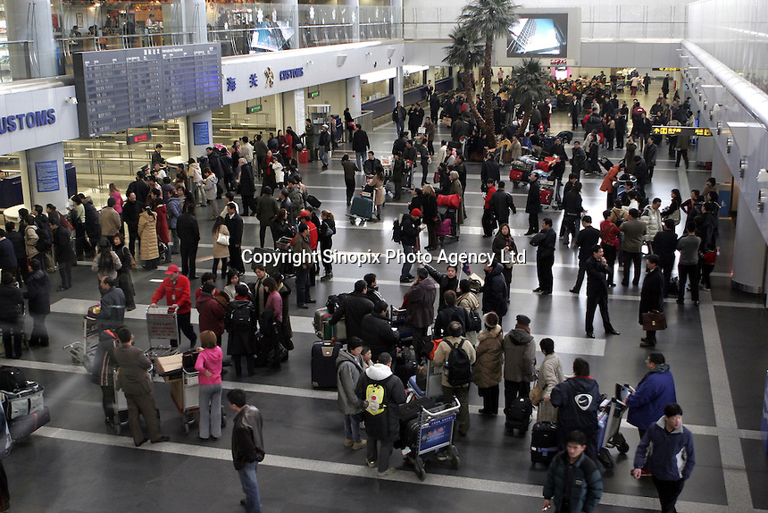 Passengers crowd the departure hall of the Beijing International Airport, China..12 Jan 2005